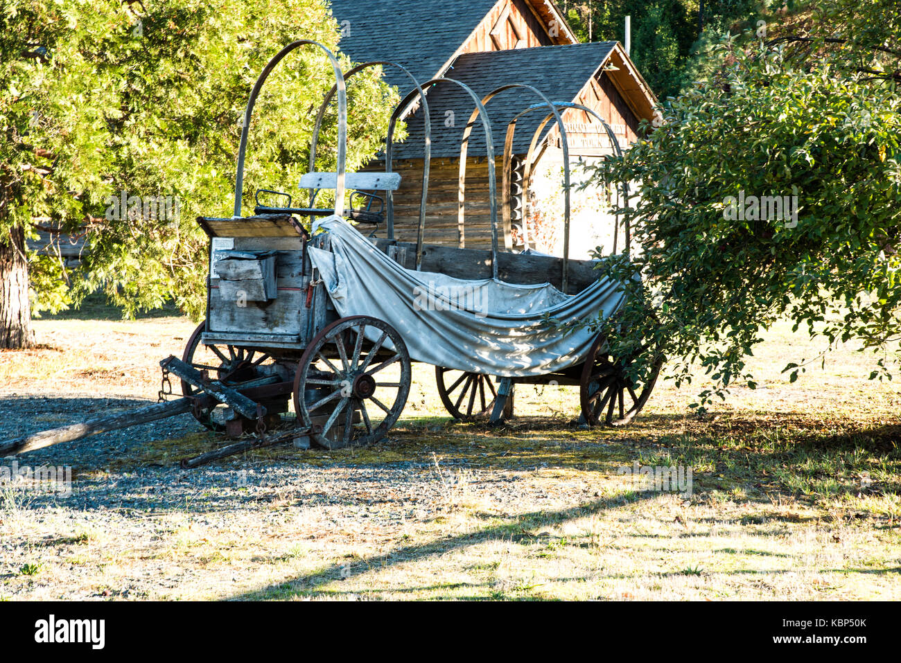 Sagging Conestoga Many Miles-An ancient covered wagon sits quietly, remembering the many miles it has traveled, - Stock Image