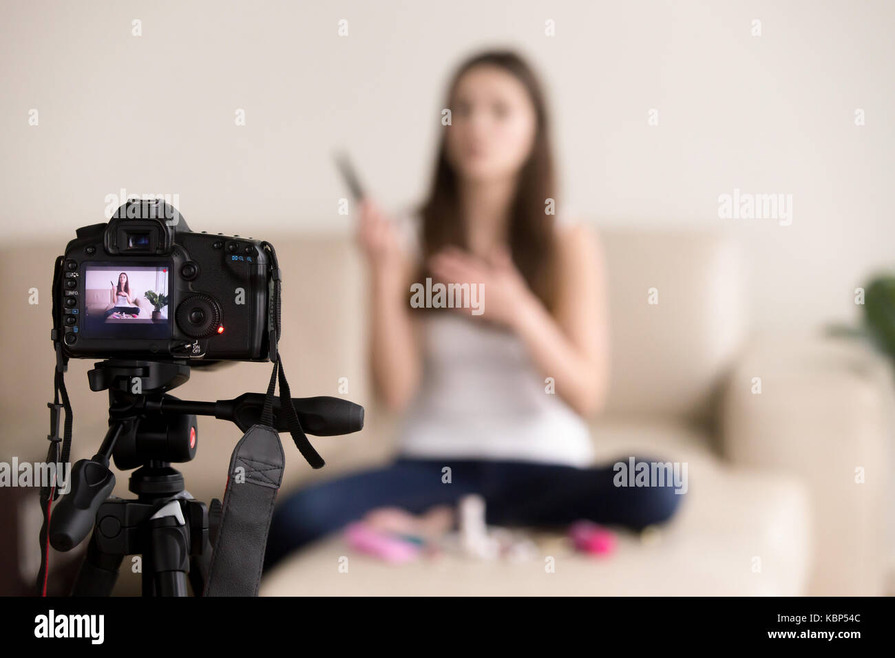 Young female videoblogger recording product review for blog. - Stock Image