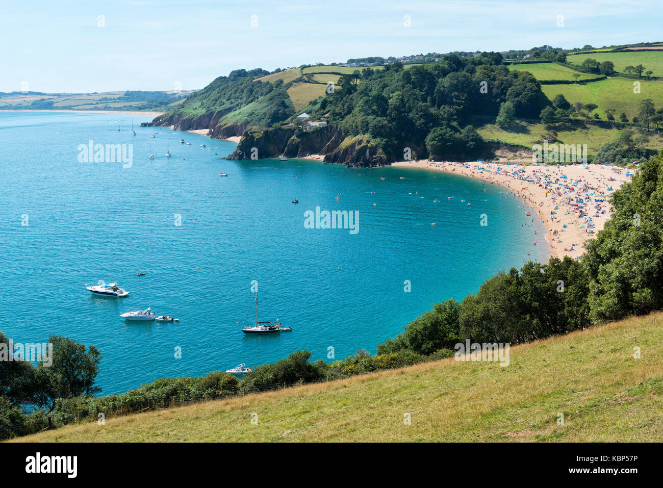 Crowded sandy beach at Blackpool Sands shot from Stoke Fleming with pleasure craft in the blue waters of the bay - Stock Image