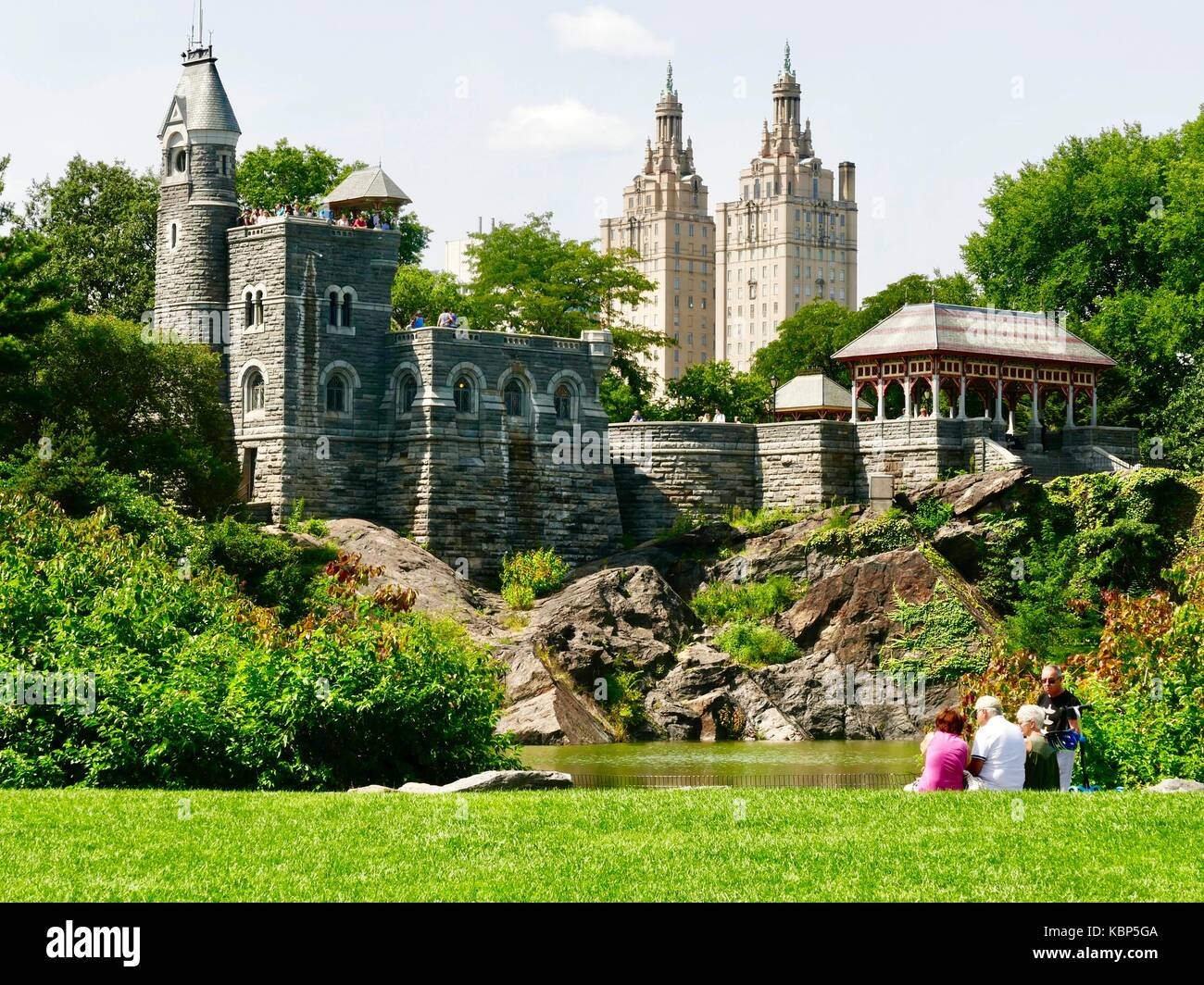 Mature adults relax at edge of Central Park Turtle Pond, visitors overlook park from top of Belvedere Castle, late - Stock Image
