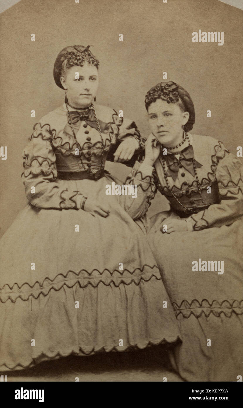 American archive monochrome studio portrait photograph of two young women wearing matching embroidered dresses, - Stock Image
