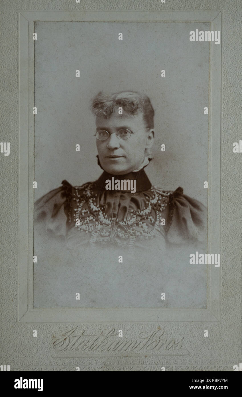American archive monochrome studio portrait photograph of an older woman with glasses wearing a dark high collared - Stock Image