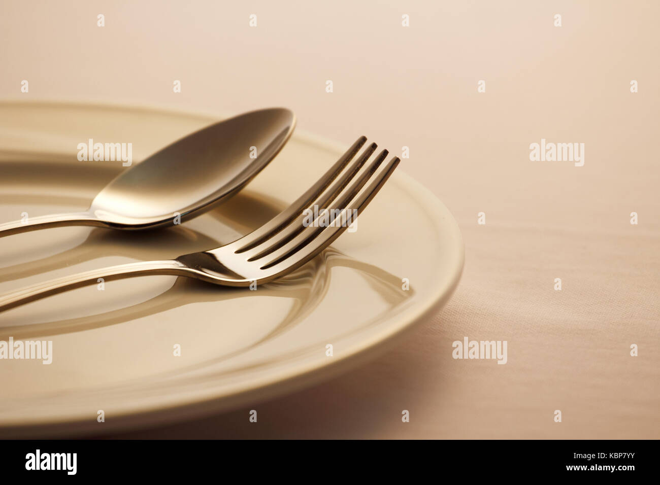 Spoon and fork on the dish - Stock Image