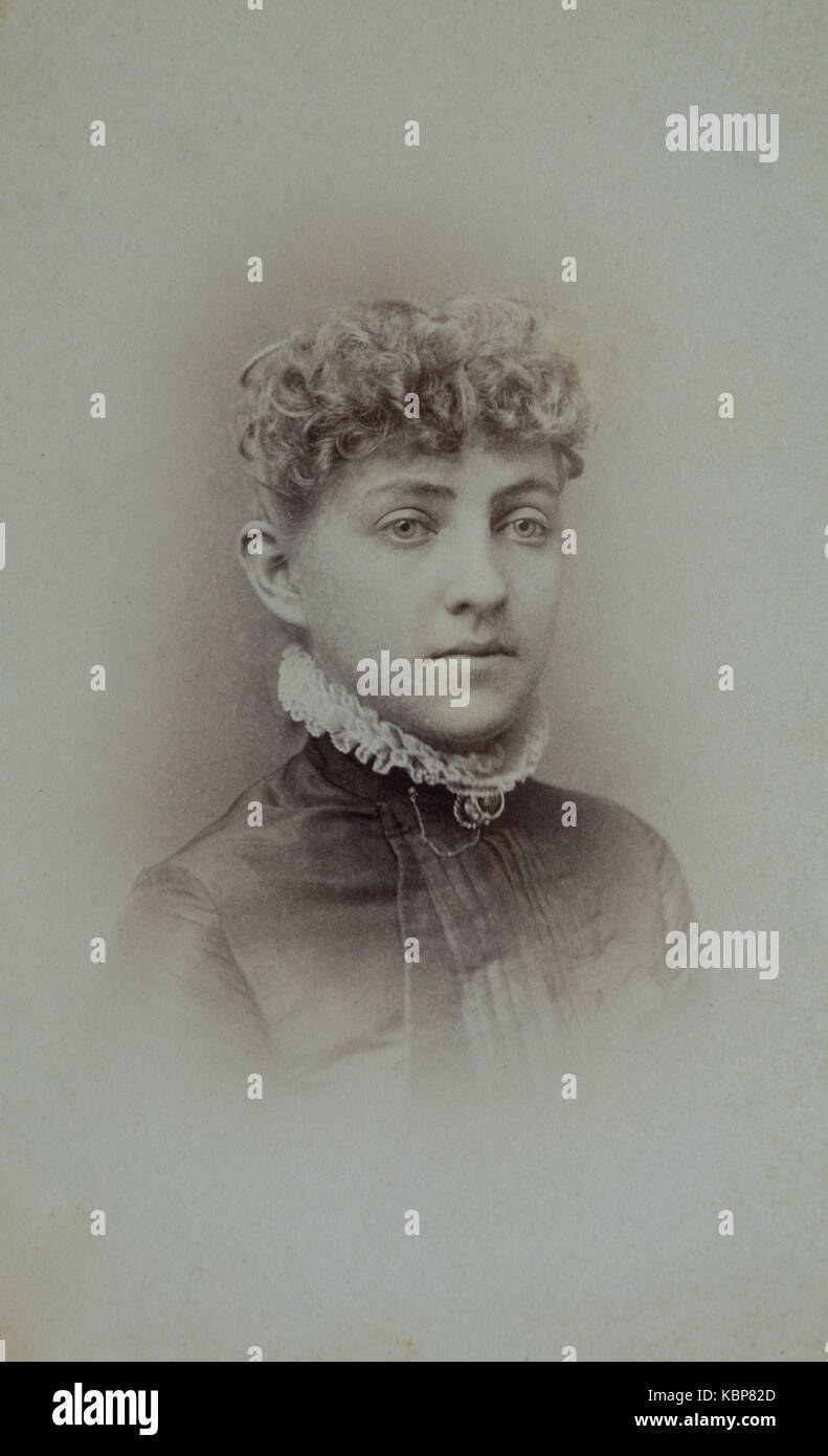 American archive monochrome studio portrait photograph of a young woman with curly hair wearing a dark coloured - Stock Image
