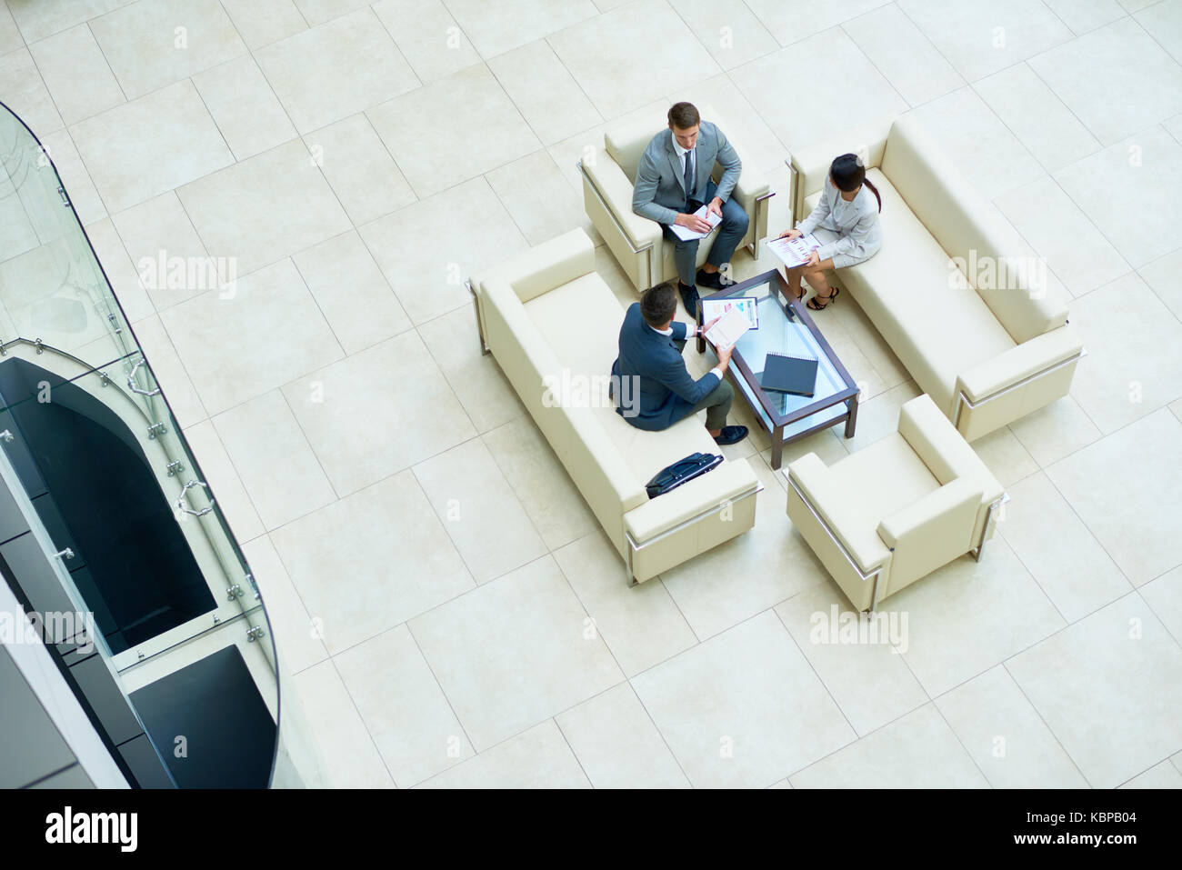 Directly above view of concentrated managers in formalwear analyzing financial figures while having informal working - Stock Image