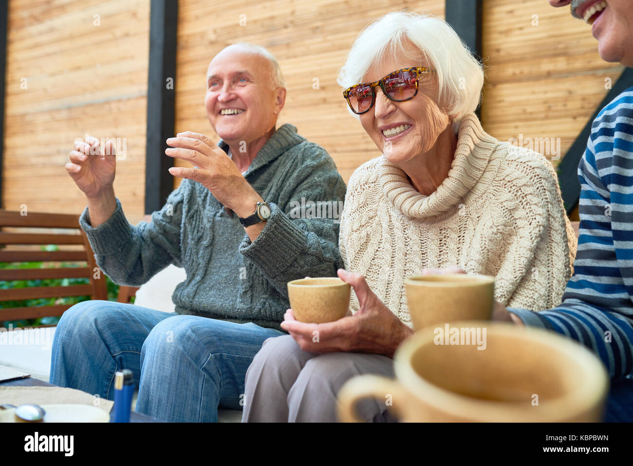Cheerful senior friends gathered together at cozy small patio and remembering funny stories from their past, they - Stock Image