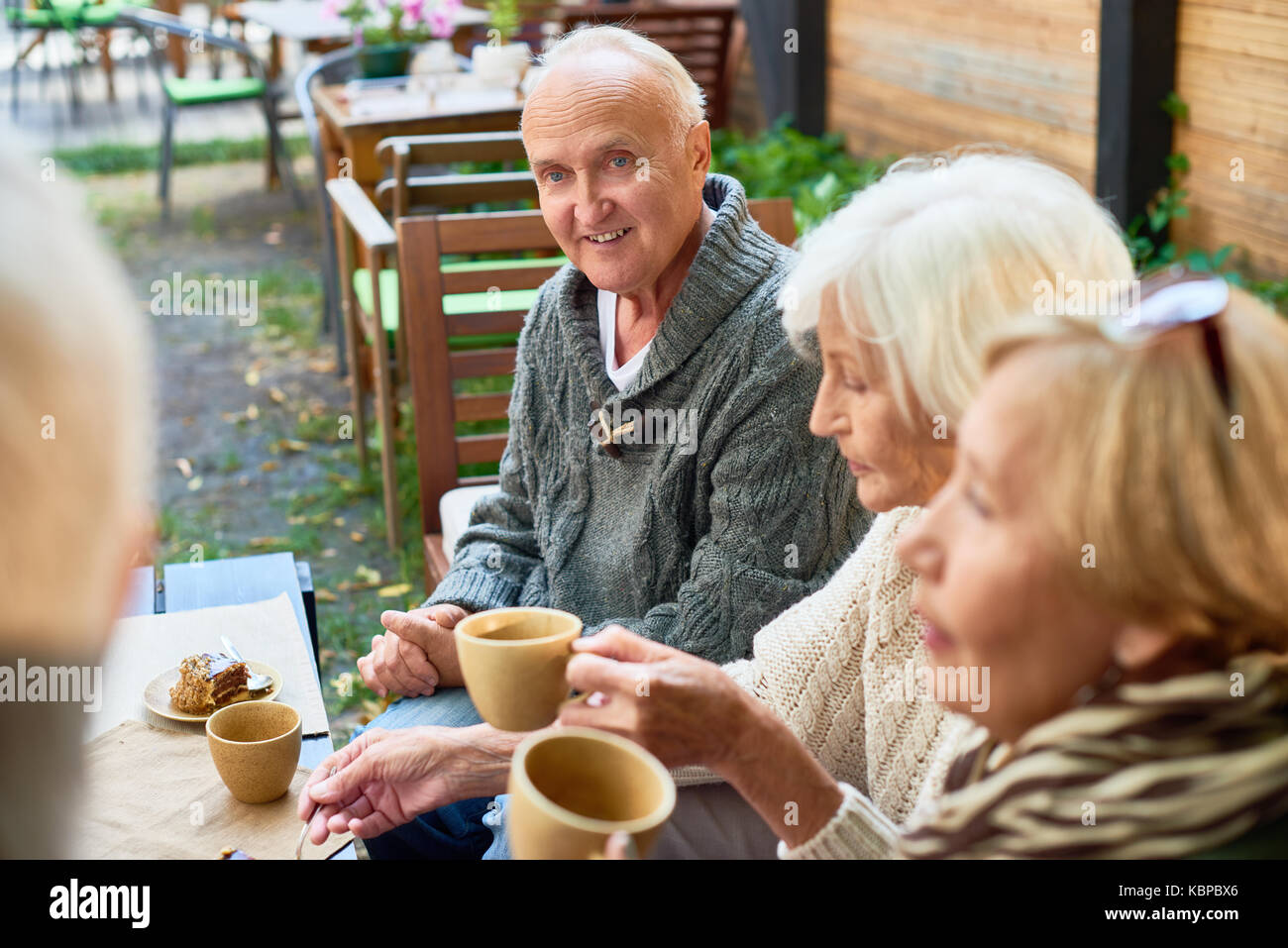 Portrait of handsome senior man with deep blue eyes listening to his friend with interest while having good time - Stock Image