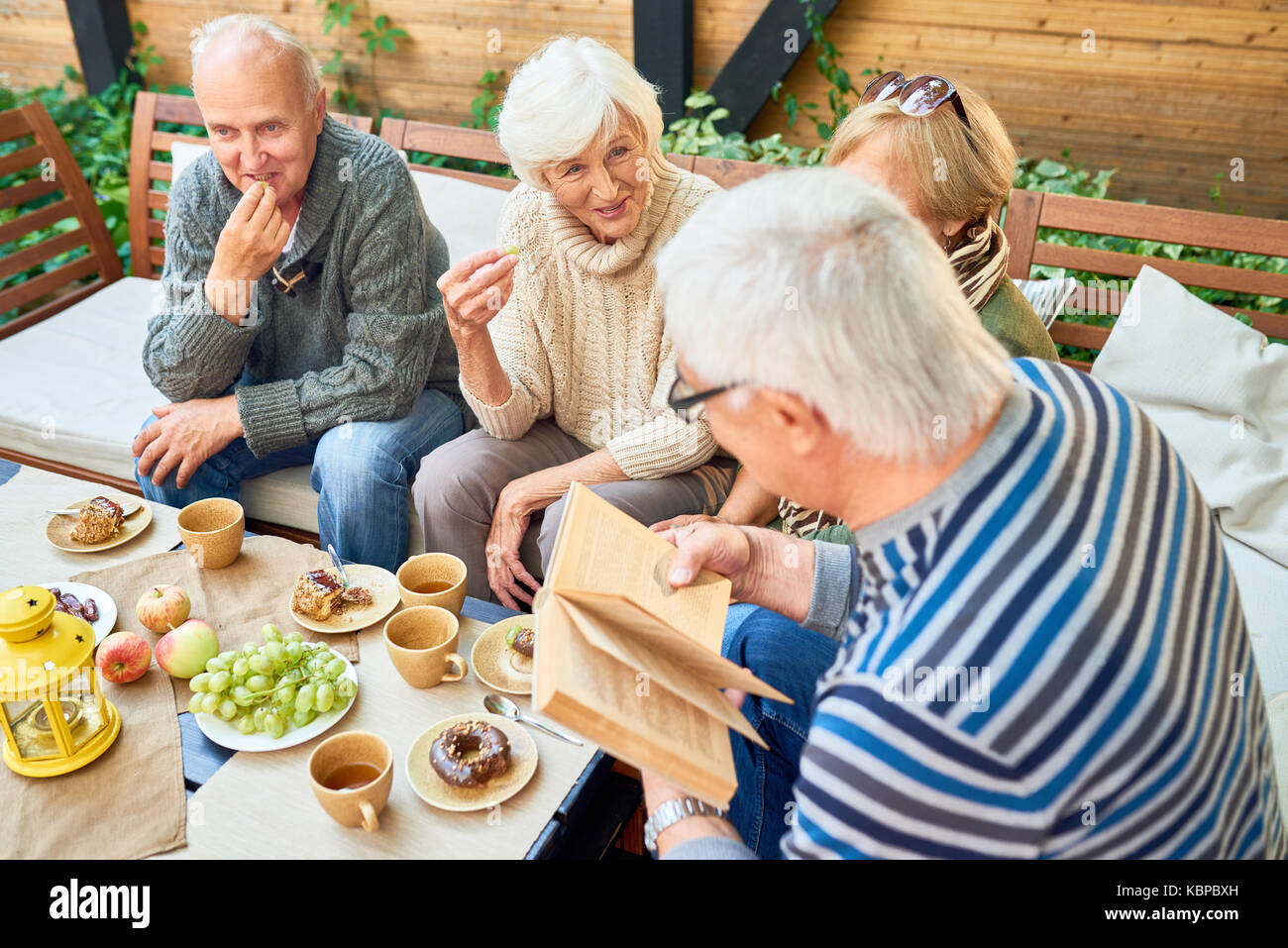 Group of joyful senior friends having fun outdoors: they enjoying delicious pastry and fragrant coffee while elderly - Stock Image