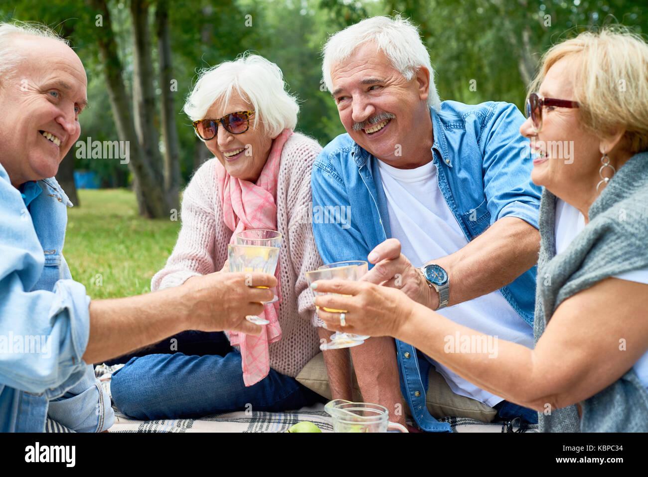 Two joyful senior couples toasting with glasses of orange juice while celebrating momentous event at green park Stock Photo