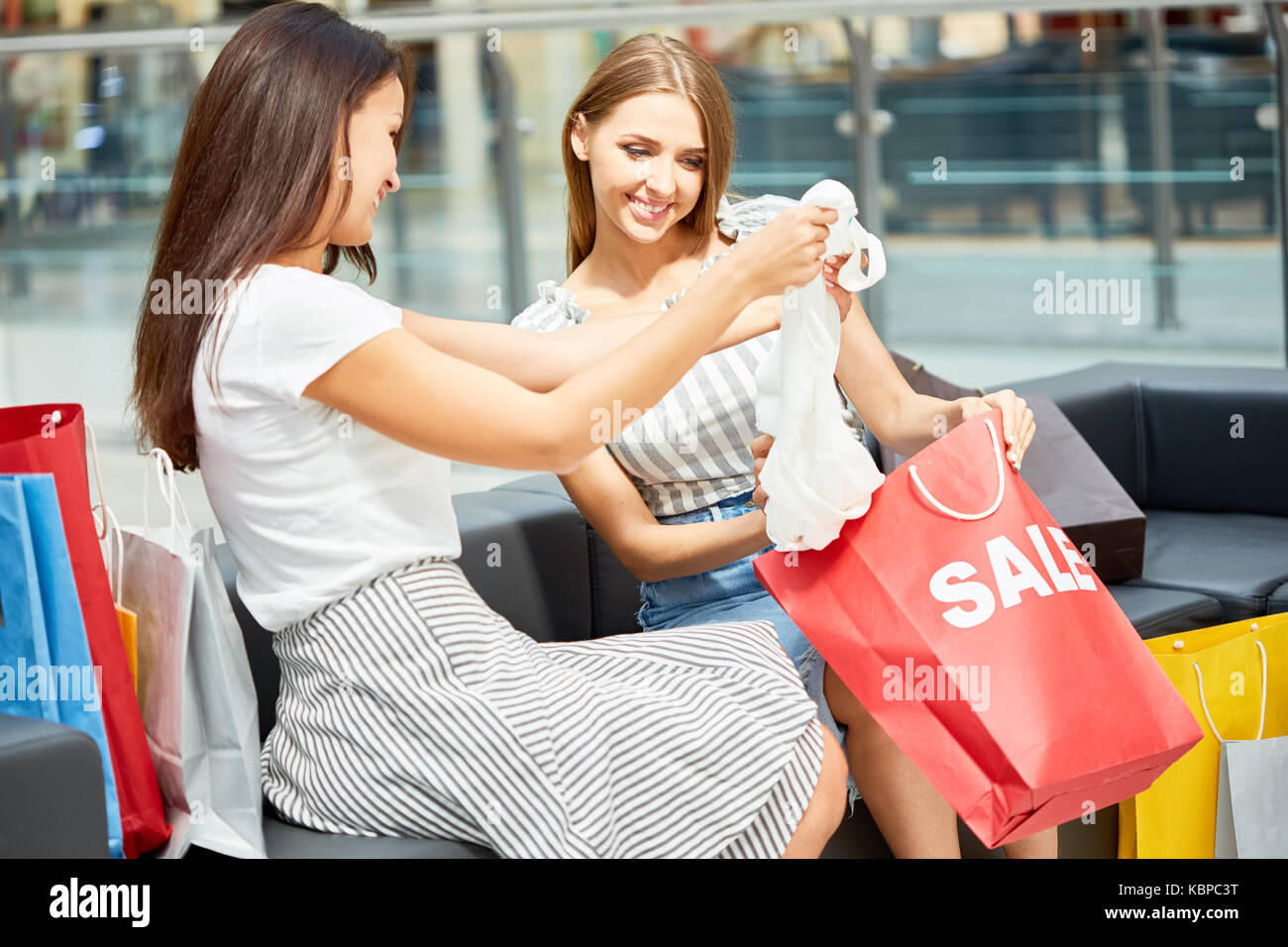 Portrait of two happy women in shopping mall, looking at clothes bought on SALE, holding red paper bags - Stock Image