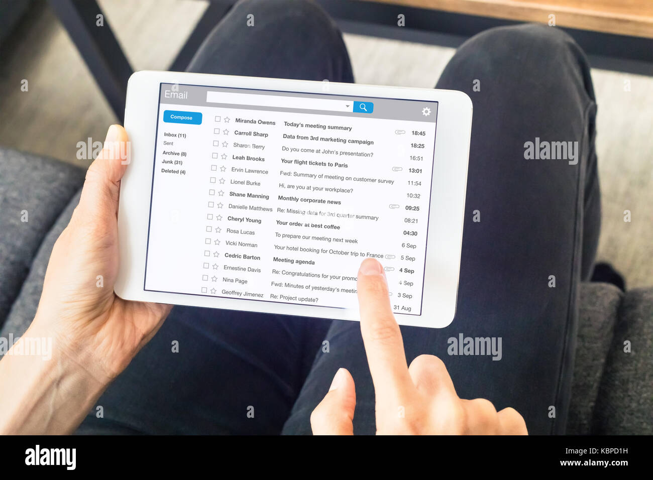 Person reading email messages in inbox at home on digital tablet computer with wireless internet, close-up of device - Stock Image