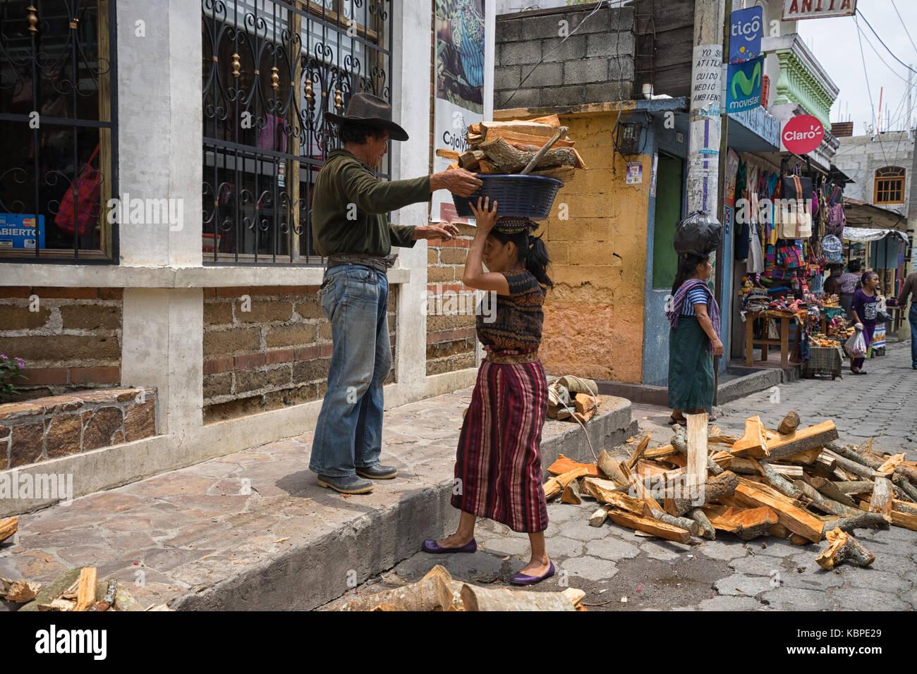 April 30, 2016 Santiago de Atitlan, Guatemala: man loads a basket full of firewood on the top of a woman's head - Stock Image