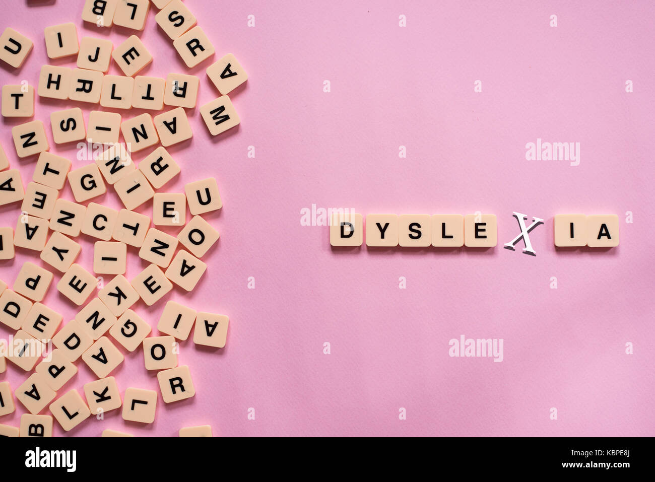 dyslexia concept - alphabet letters on pink background - Stock Image