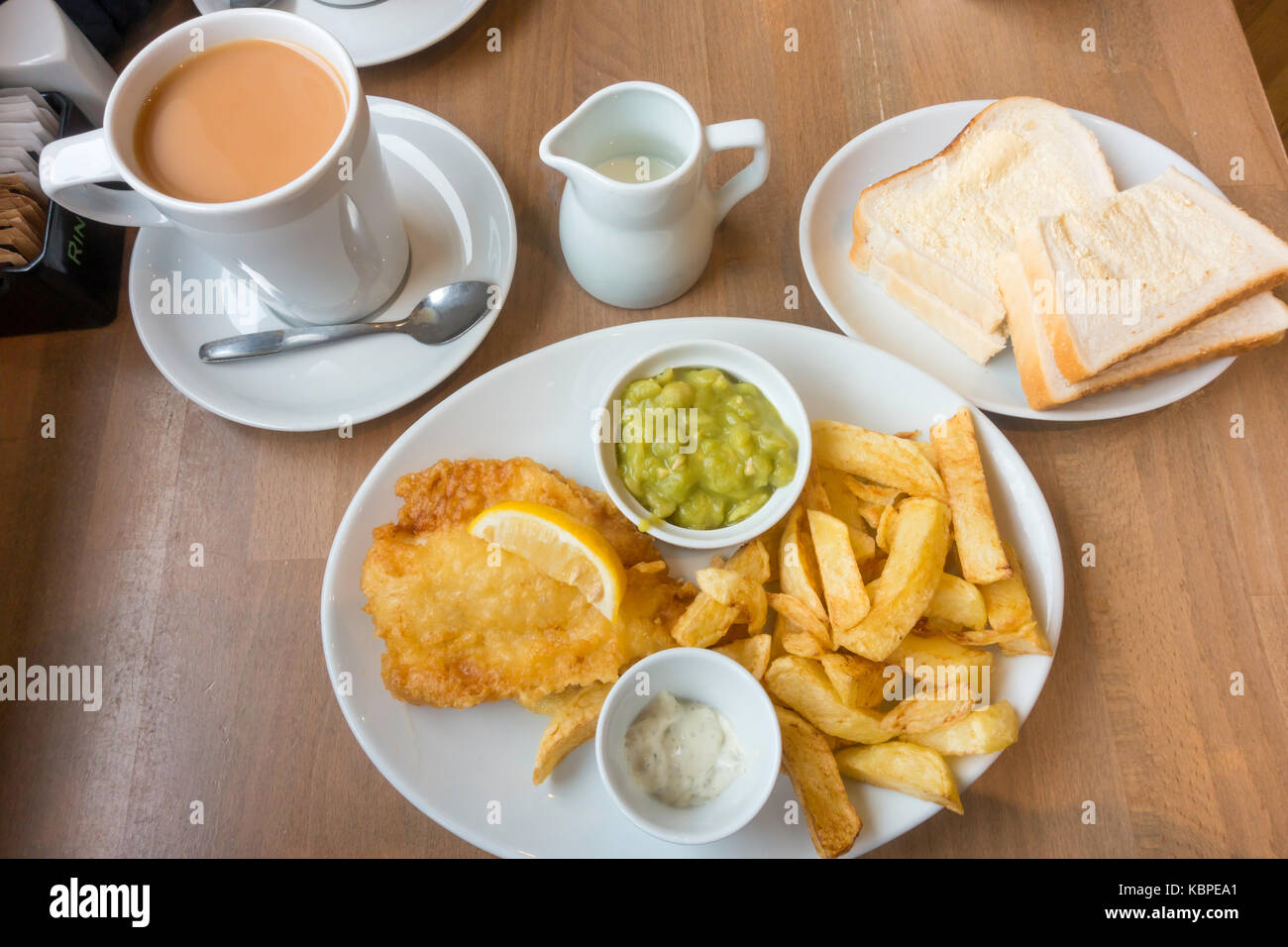 Over sixties Special Fish and Chips a small portion of Cod with mushy peas bread and butter cup of tea traditional - Stock Image