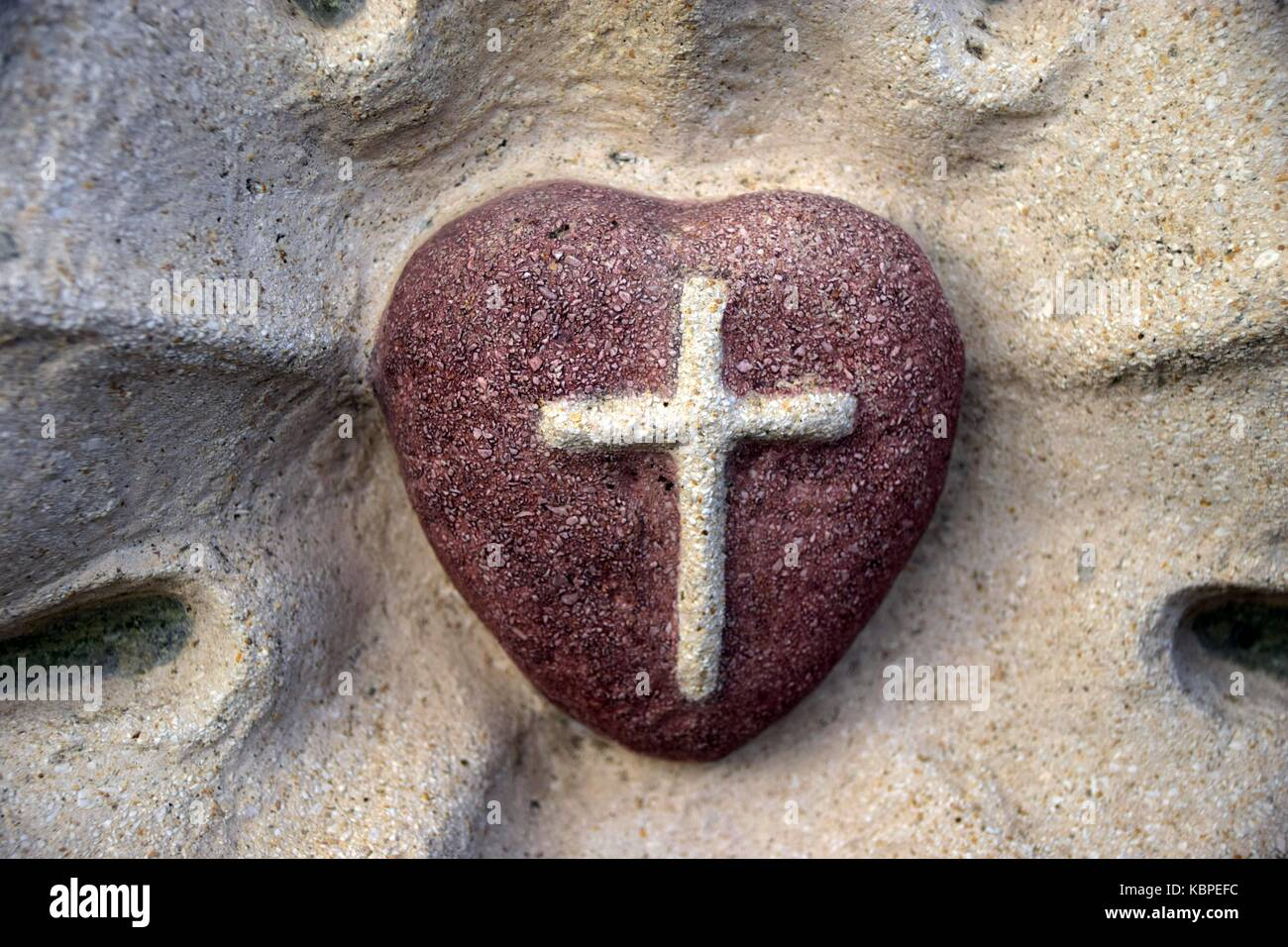 a red heart made of sandstone, a cross in the middle, Symbol of love, Christian Symbol, bas-relief, basalt relief, - Stock Image