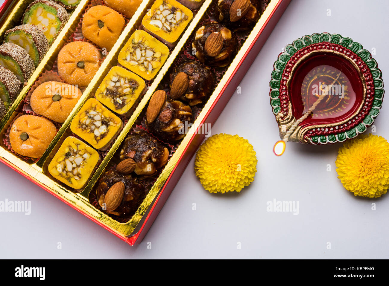 stock photo of Indian sweet or mithai and oil lamp or diya with gift box and flowers on decorative or colourful - Stock Image
