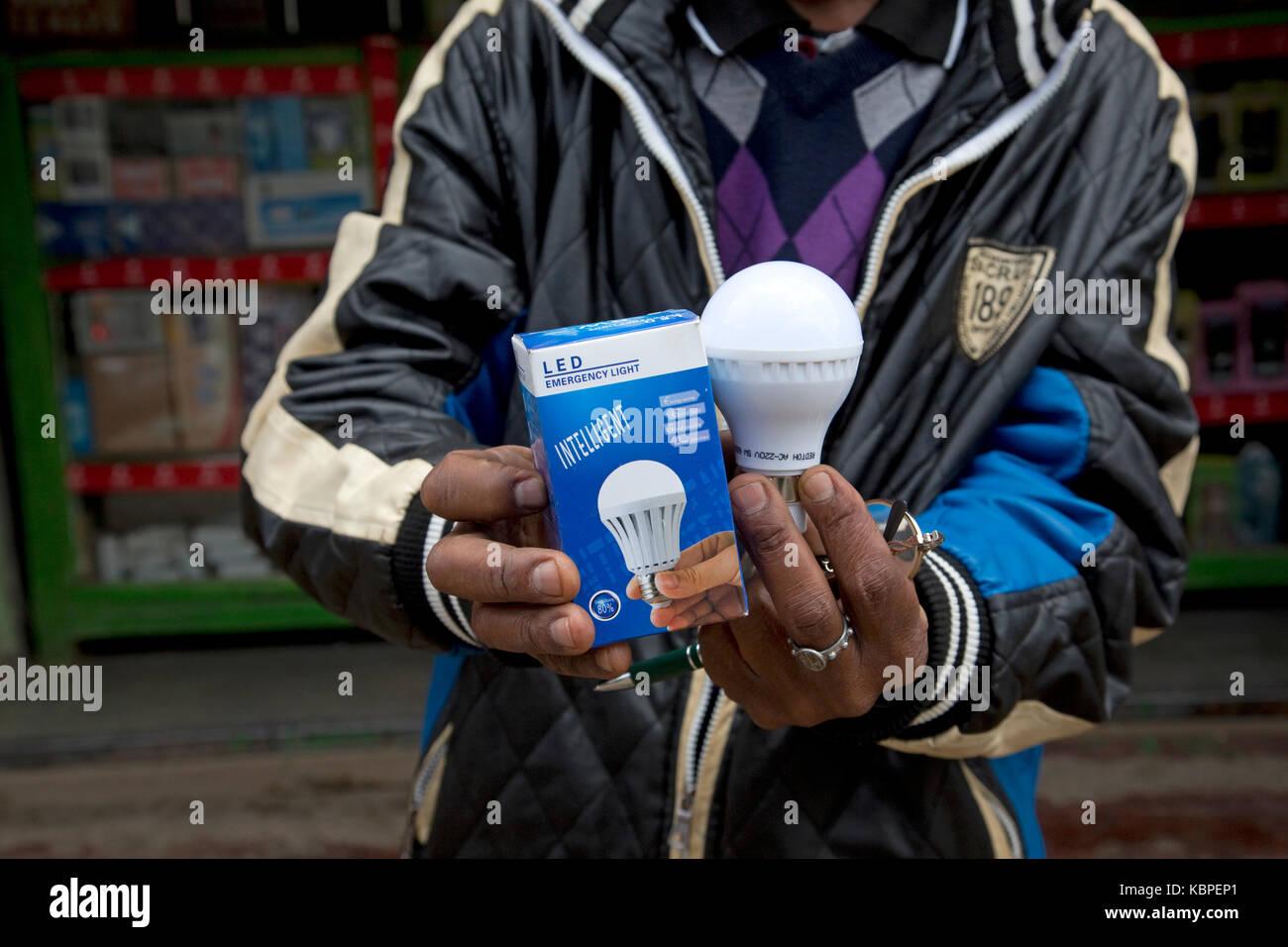 African man holding intelligent energy effiicient LED lamps outside duka in Kamere Township Kenya - Stock Image