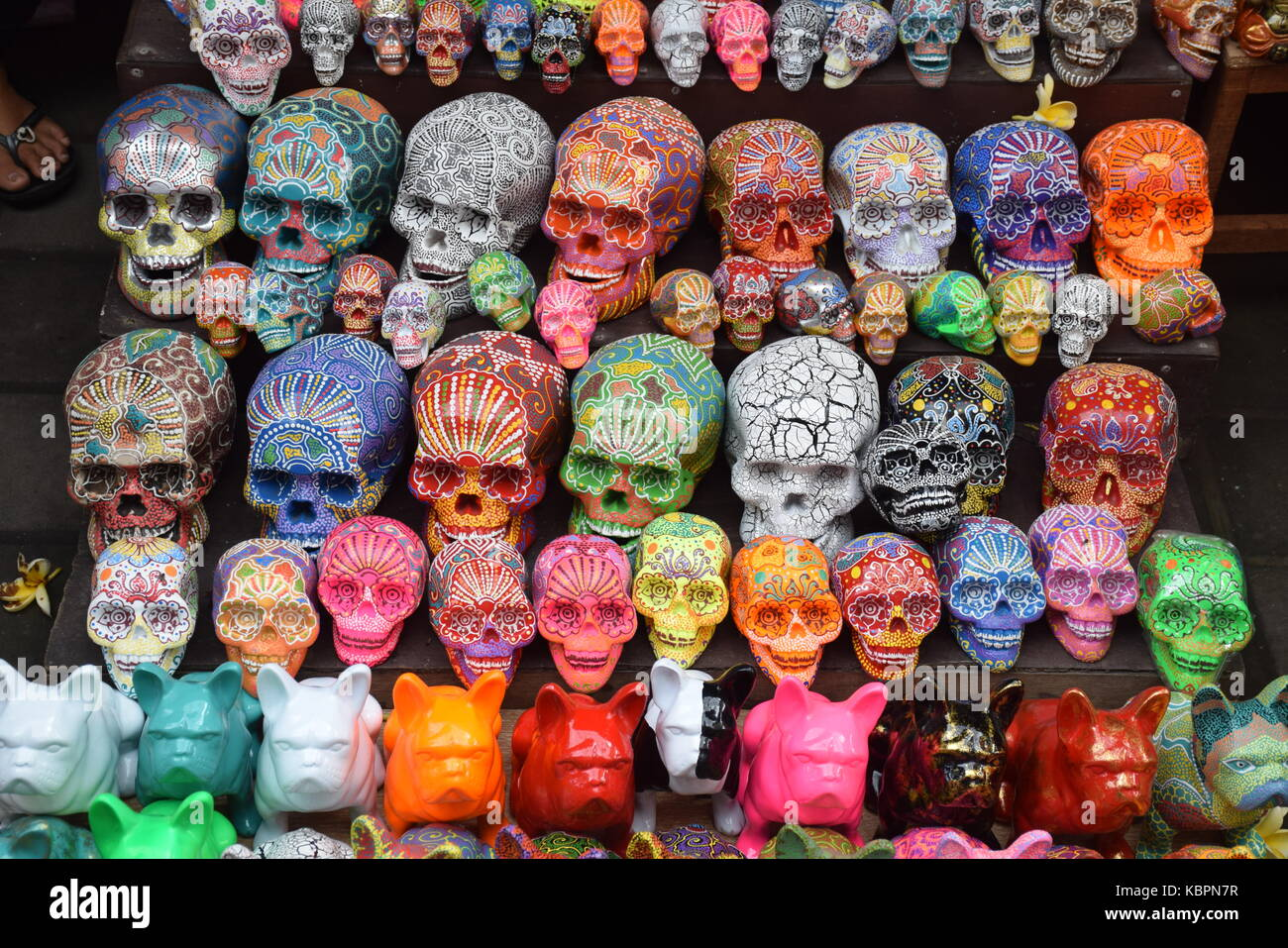 Colorful skulls sold in a shop in Ubud market in Bali, Indonesia - Stock Image