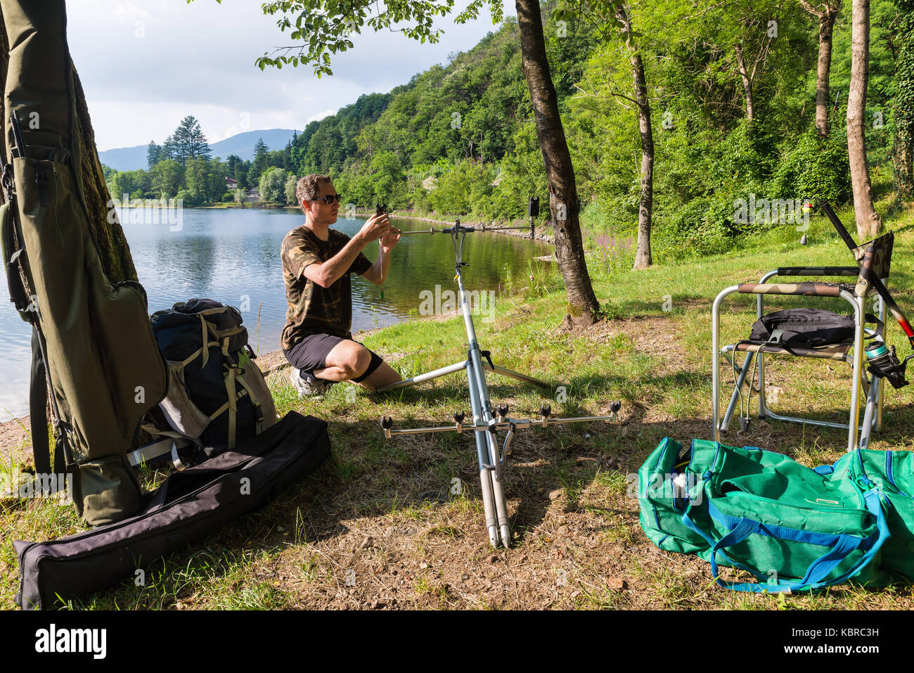 Fishing adventures, carp fishing. Angler with camouflage t-shirt, is fishing with carpfishing technique in freshwater. - Stock Image
