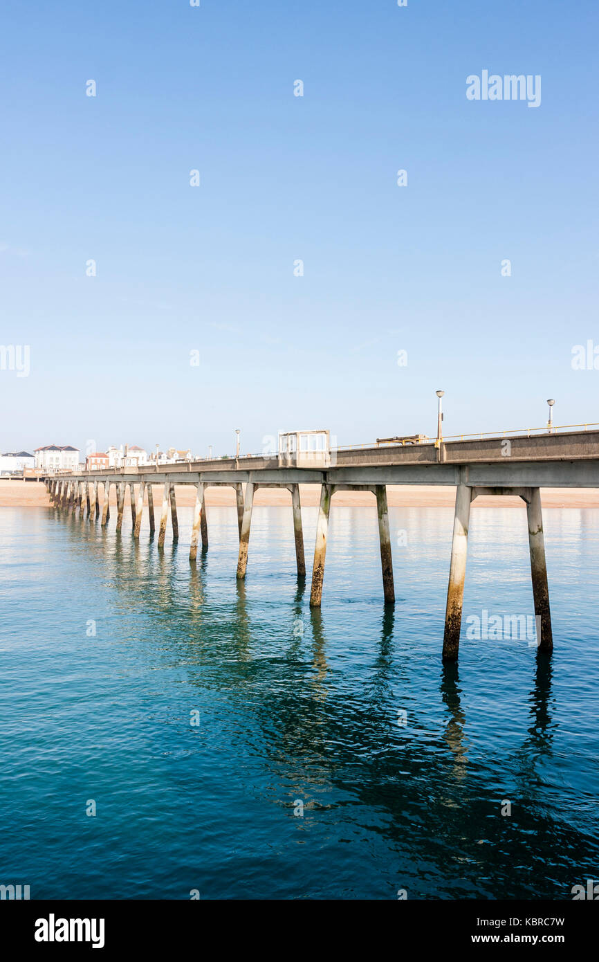 England, Deal pier. View of length of pier and beach with part of the town. Clear blue sky, daytime, bright sunshine. - Stock Image
