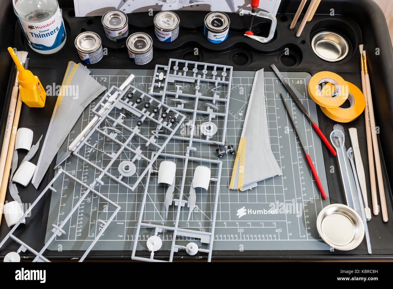 England. Modelling station with cutting mat, paint pots, tools, maskign tape. Spur of airplane parts, and plane - Stock Image