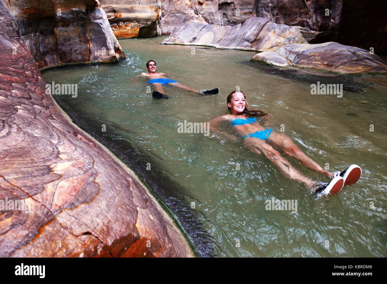 Young couple floats at the canyon of Wadi Mujib, Jordan - Stock Image