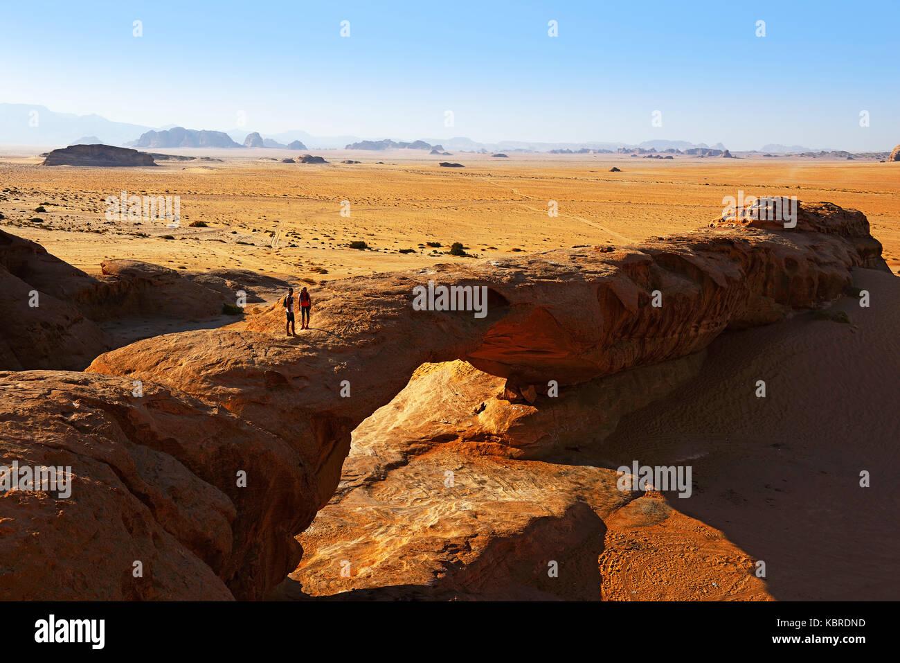 Trail runners at Rock-Arch Al Kharza, Wadi Rum, Jordan - Stock Image