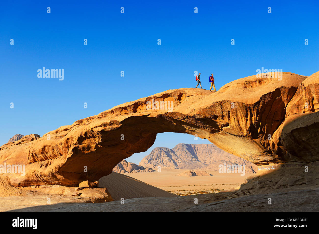 Couple hiking at Rock-Arch named Al Kharza, Wadi Rum, Jordan - Stock Image