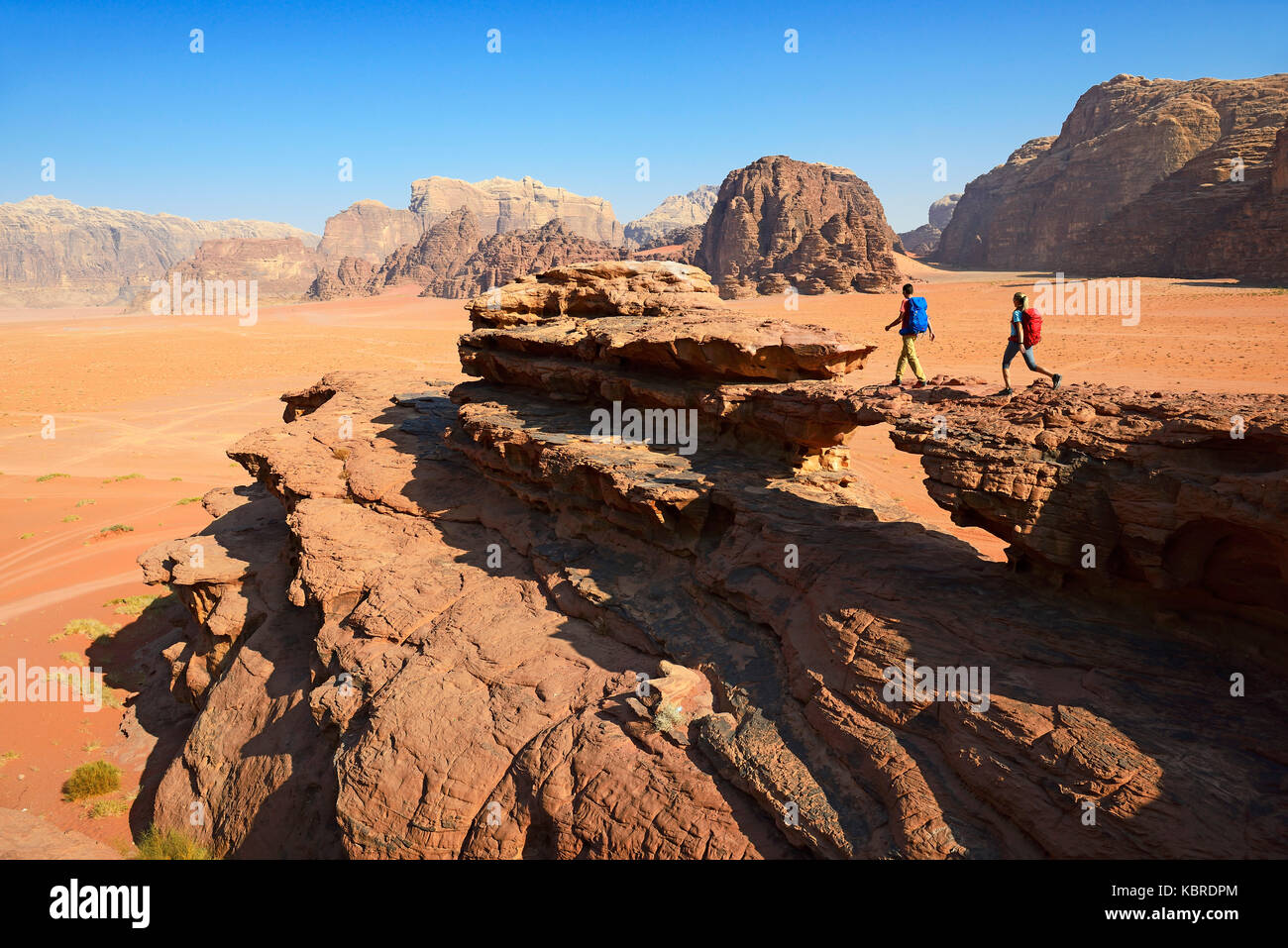 Couple hiking at Rock Arch, Al Borg Alsagheer, Wadi Rum, Jordan - Stock Image