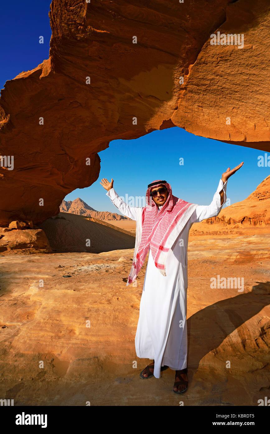 Bedouin at Rock-Arch Al Kharza, Wadi Rum, Jordan - Stock Image