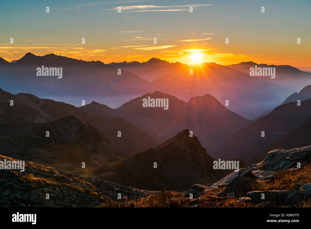 The sun rises at dawn on a mountain chain, Mont Avic Natural park, Aosta Valley, Italy - Stock Image
