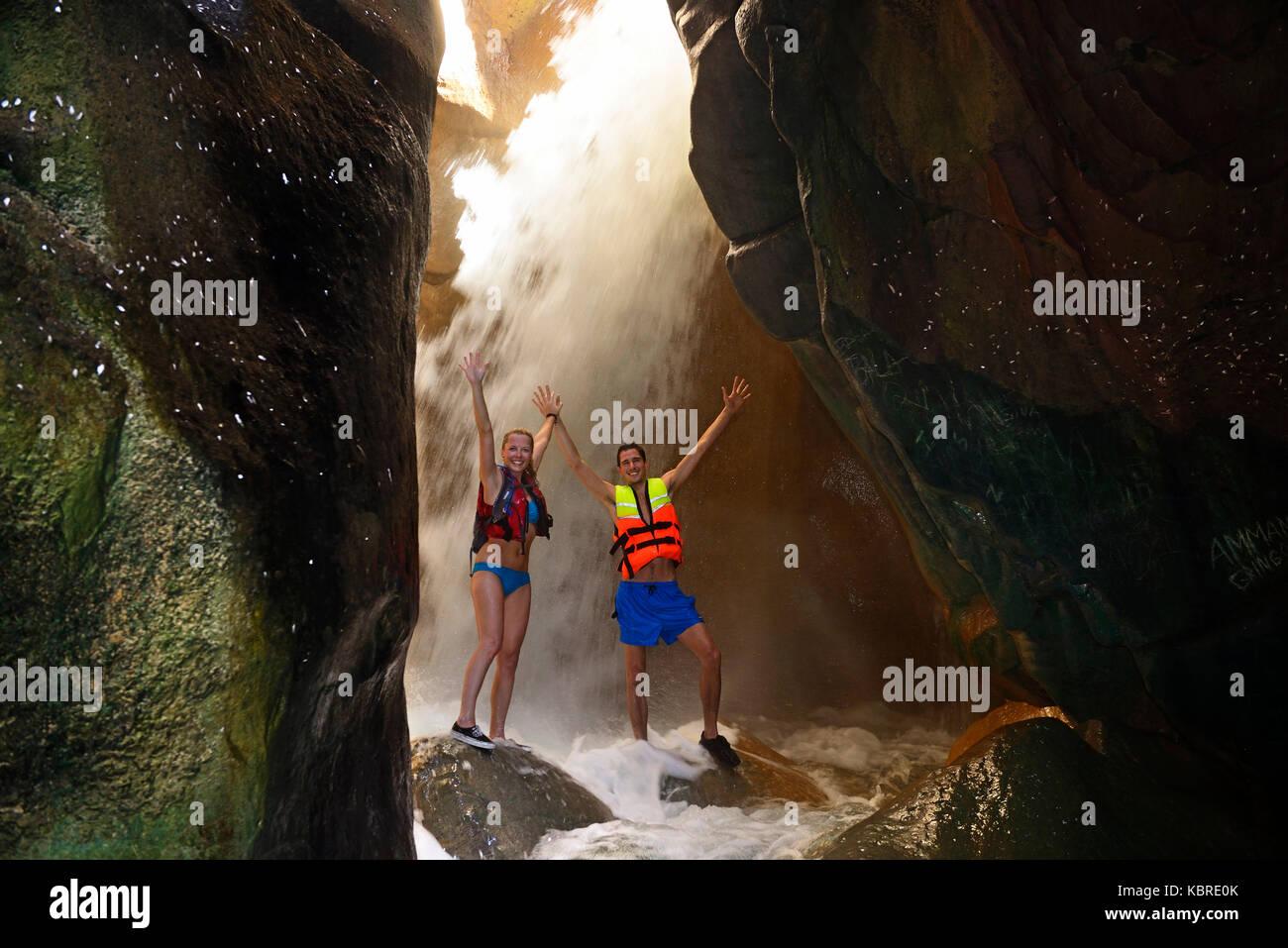 Young couple under waterfall at the canyon of Wadi Mujib, Jordan - Stock Image