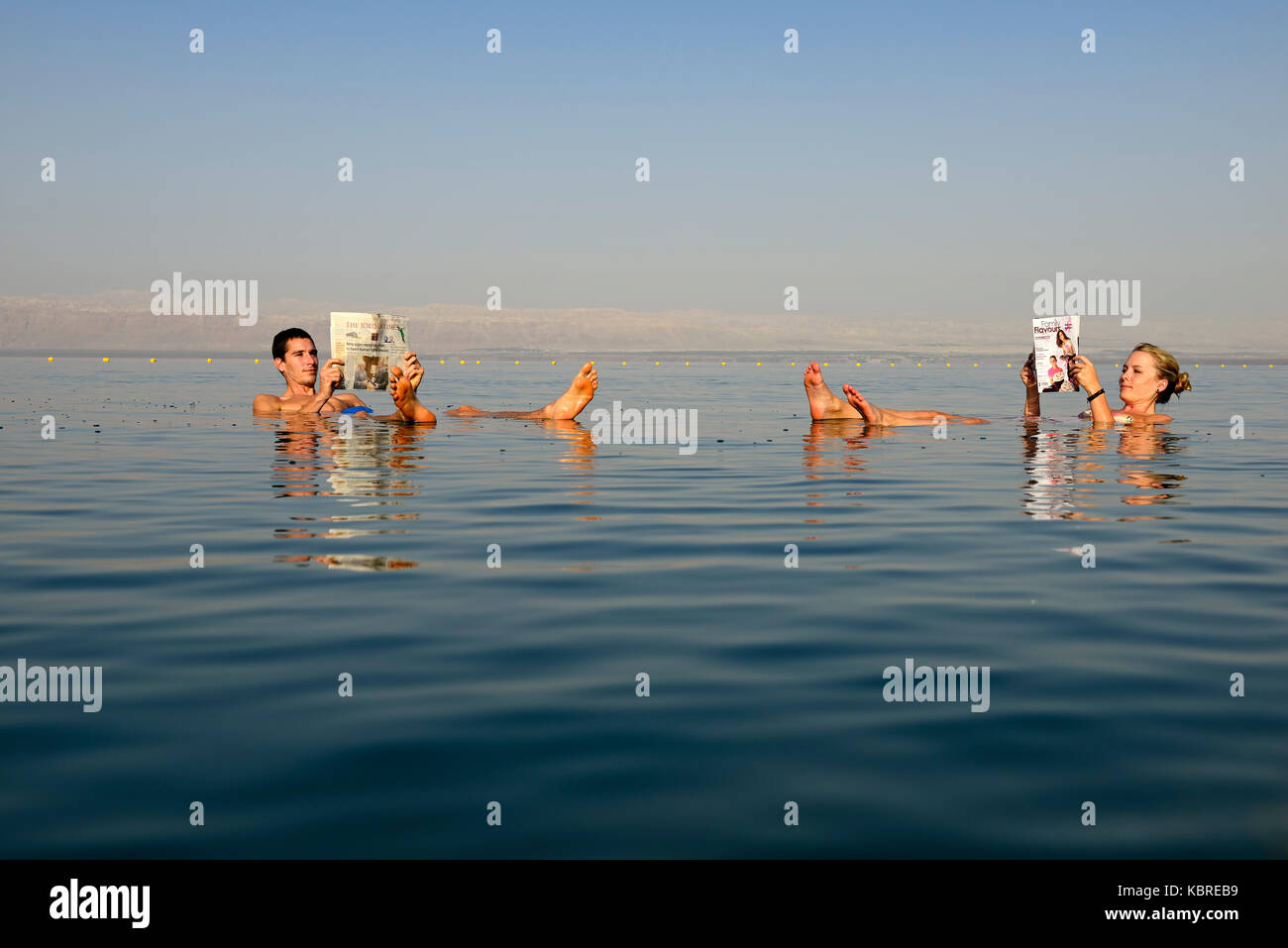 Young couple reads newspaper floating in Dead Sea, Jordan - Stock Image