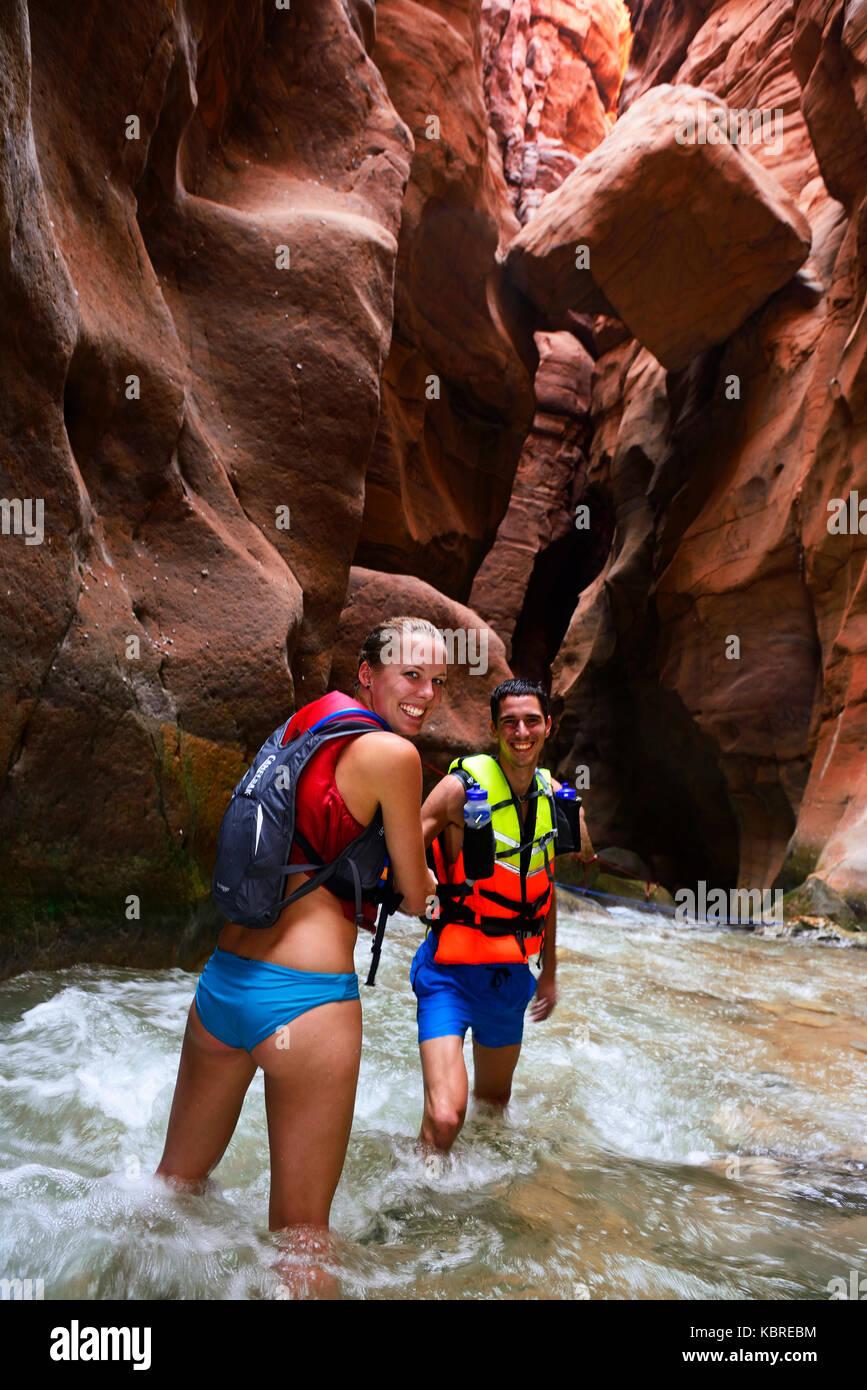 Young couple under big rock at the canyon of Wadi Mujib, Jordan - Stock Image