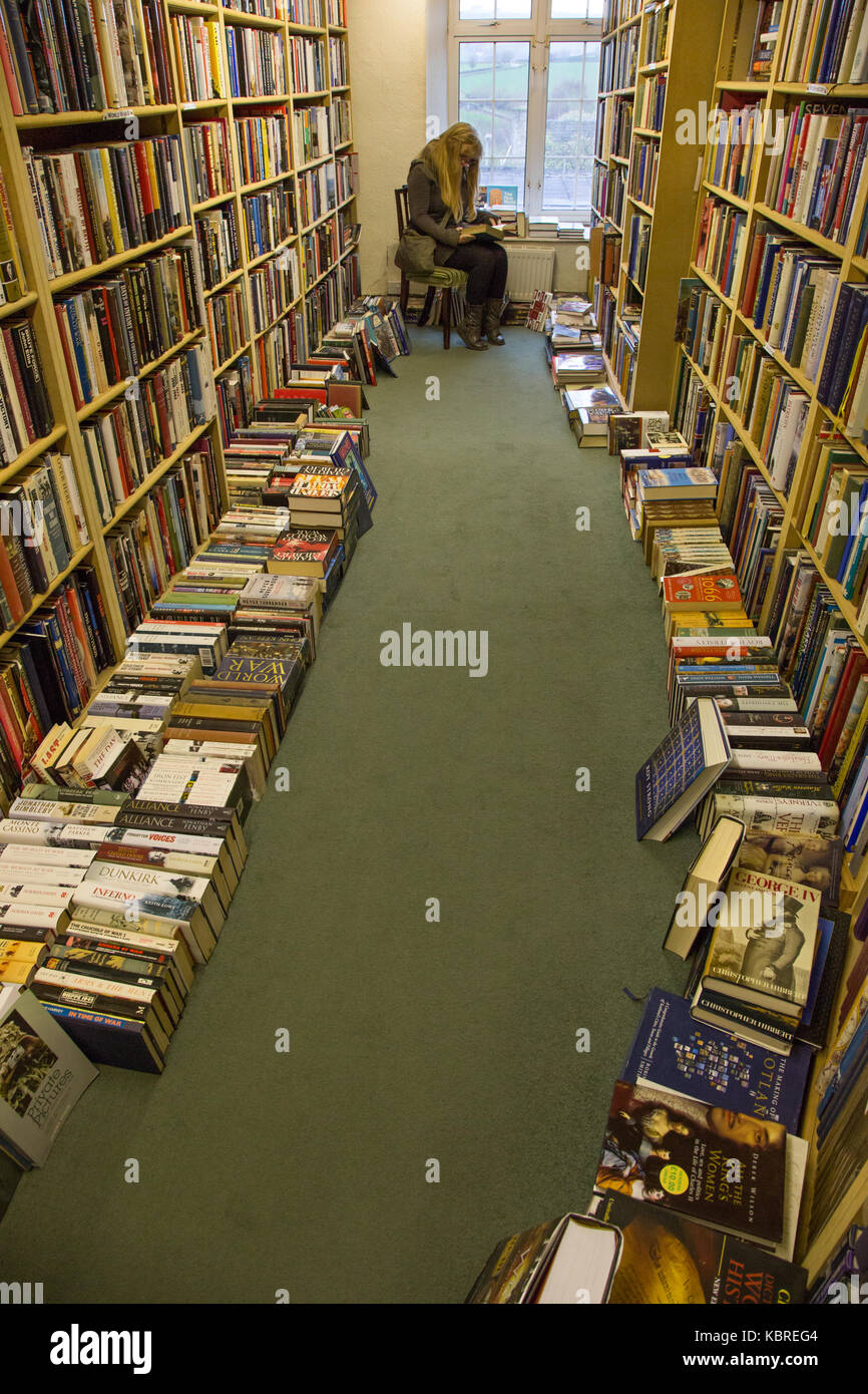 Woman reading books in secondhand bookshop - Stock Image