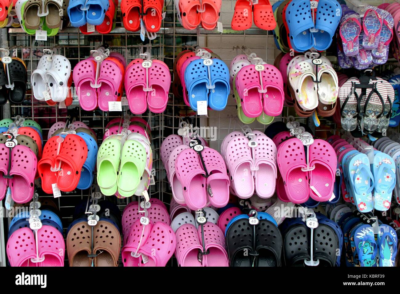 4d6d23c0c4f6b Rack with lots of pairs of childrens soft rubber sandals or  Crocs  in  various