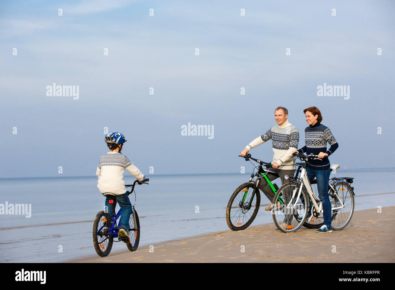 Young family of three riding bicycles on beach Stock Photo