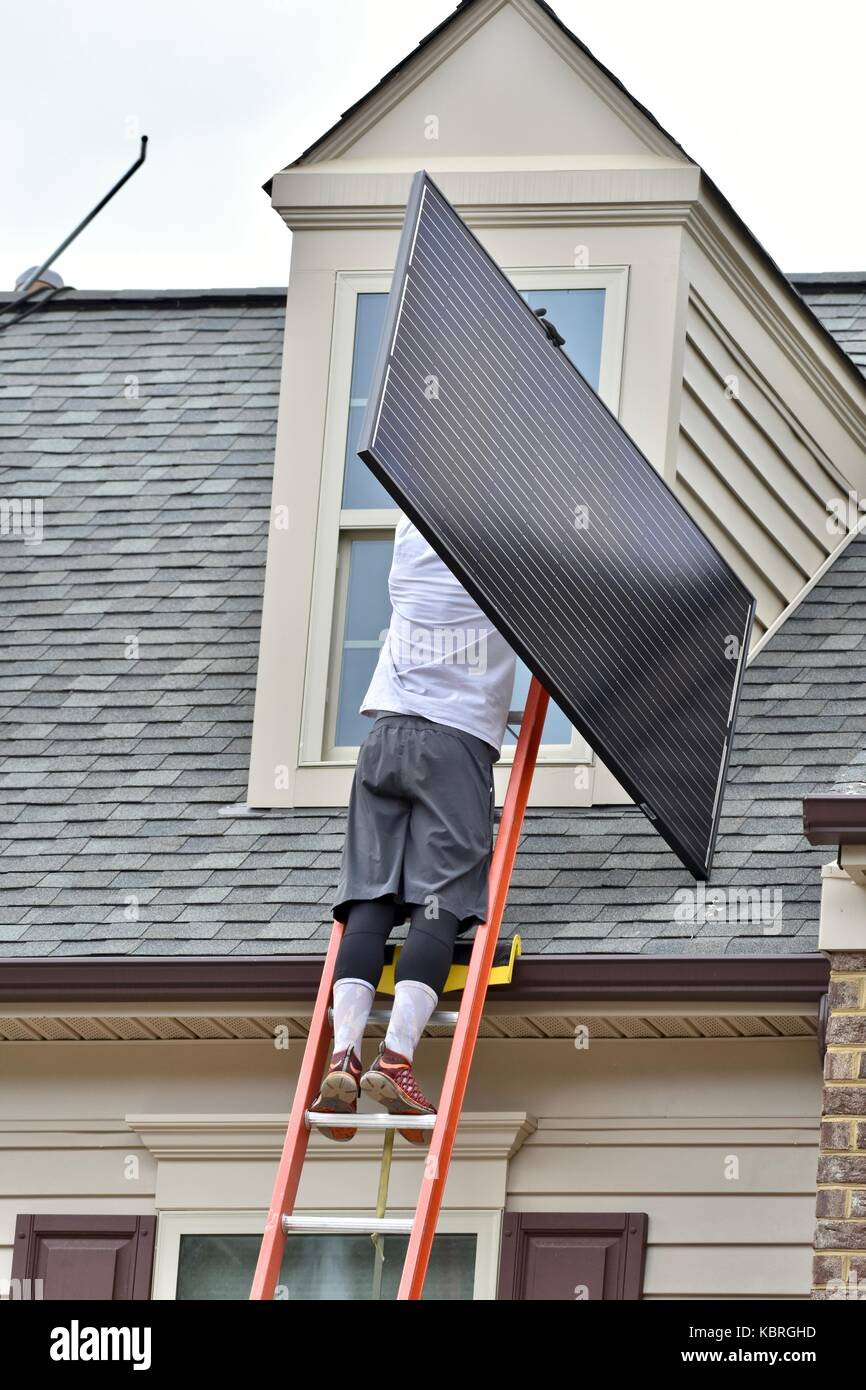 Solar Panel Technician Carrying Solar Panels Up Ladder