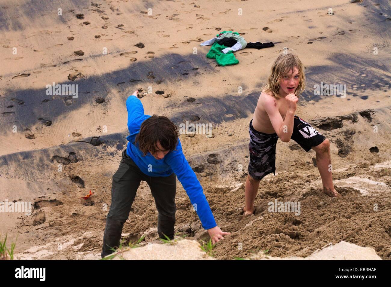 Young teenage boys running up a sandbank, Marengo Beach, Vic, Aus. - Stock Image