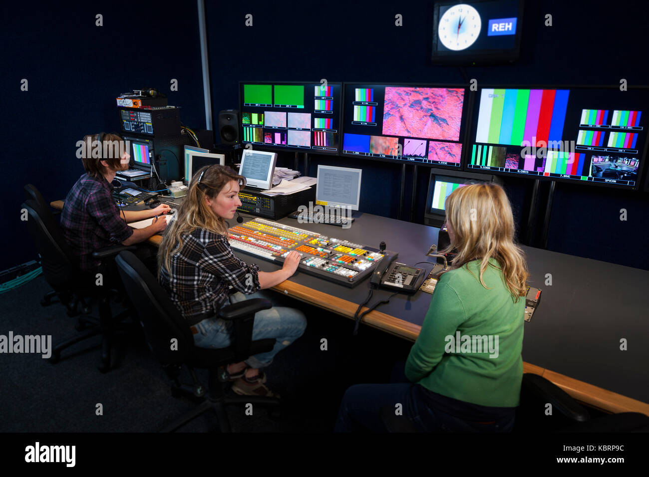 TV Director talking to her Vision Mixer in a Television Gallery. - Stock Image