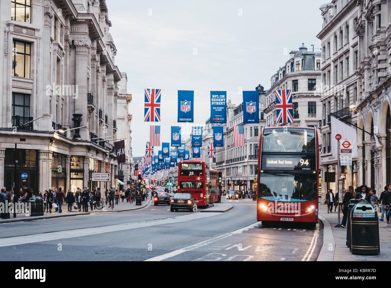 Red double-decker buses on Regent Street, London. The street is decorated with NFL flags to celebrate the event - Stock Image