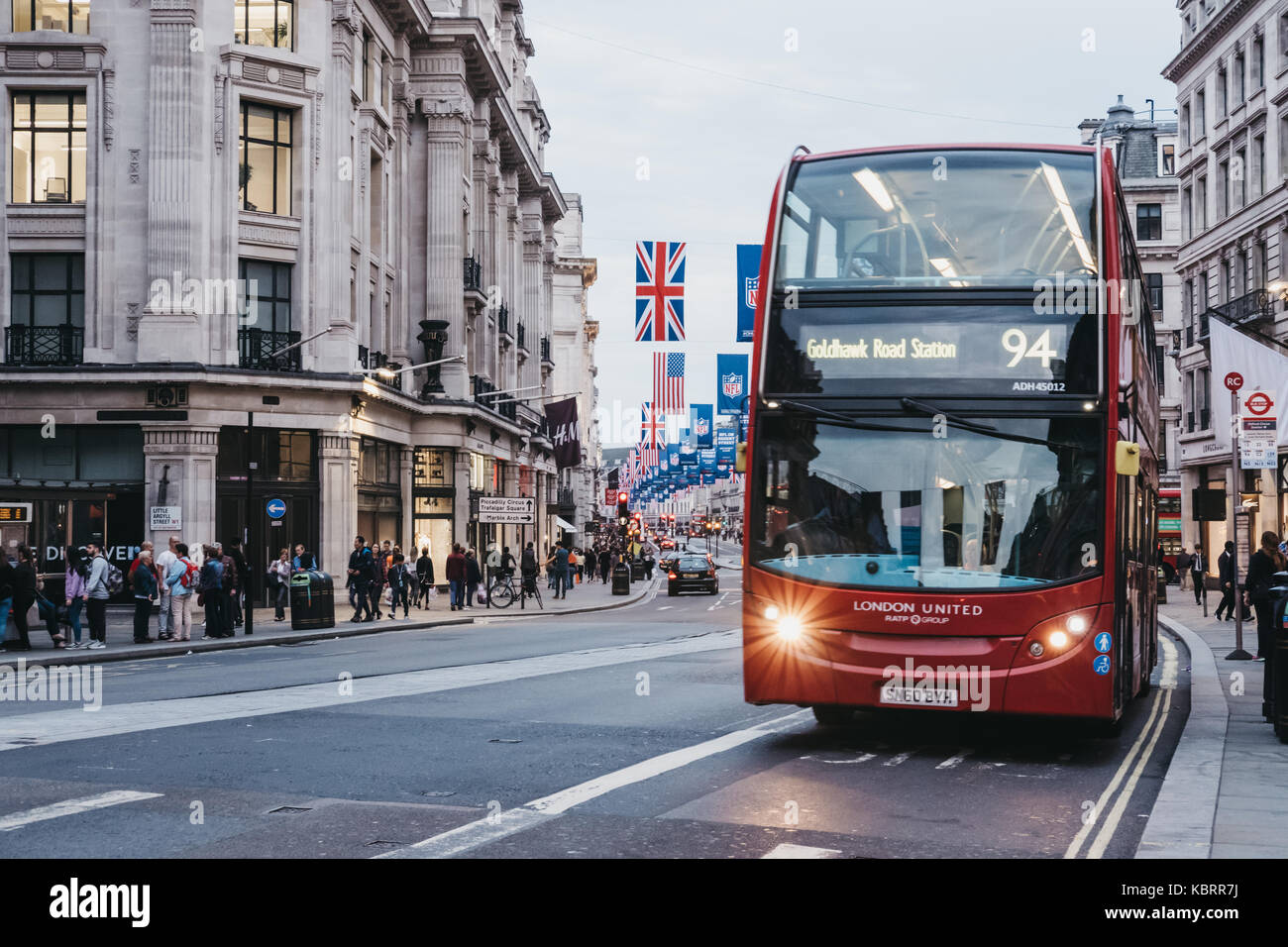 Red double-decker bus on Regent Street, London. The street is decorated with NFL flags to celebrate the event and - Stock Image