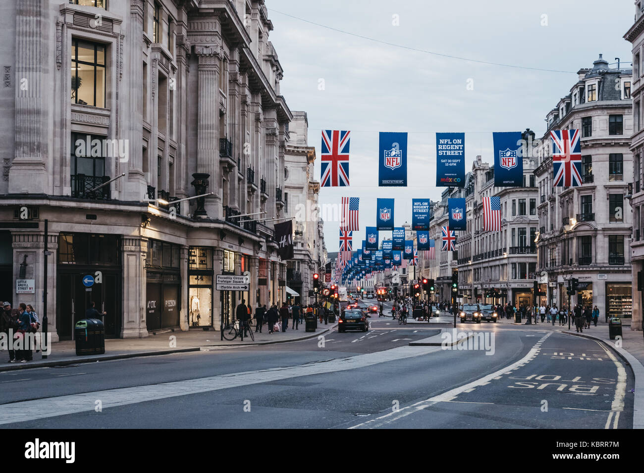 View of Regent Street, London at dusk. The street is decorated with NFL flags to celebrate the event and four NFL - Stock Image