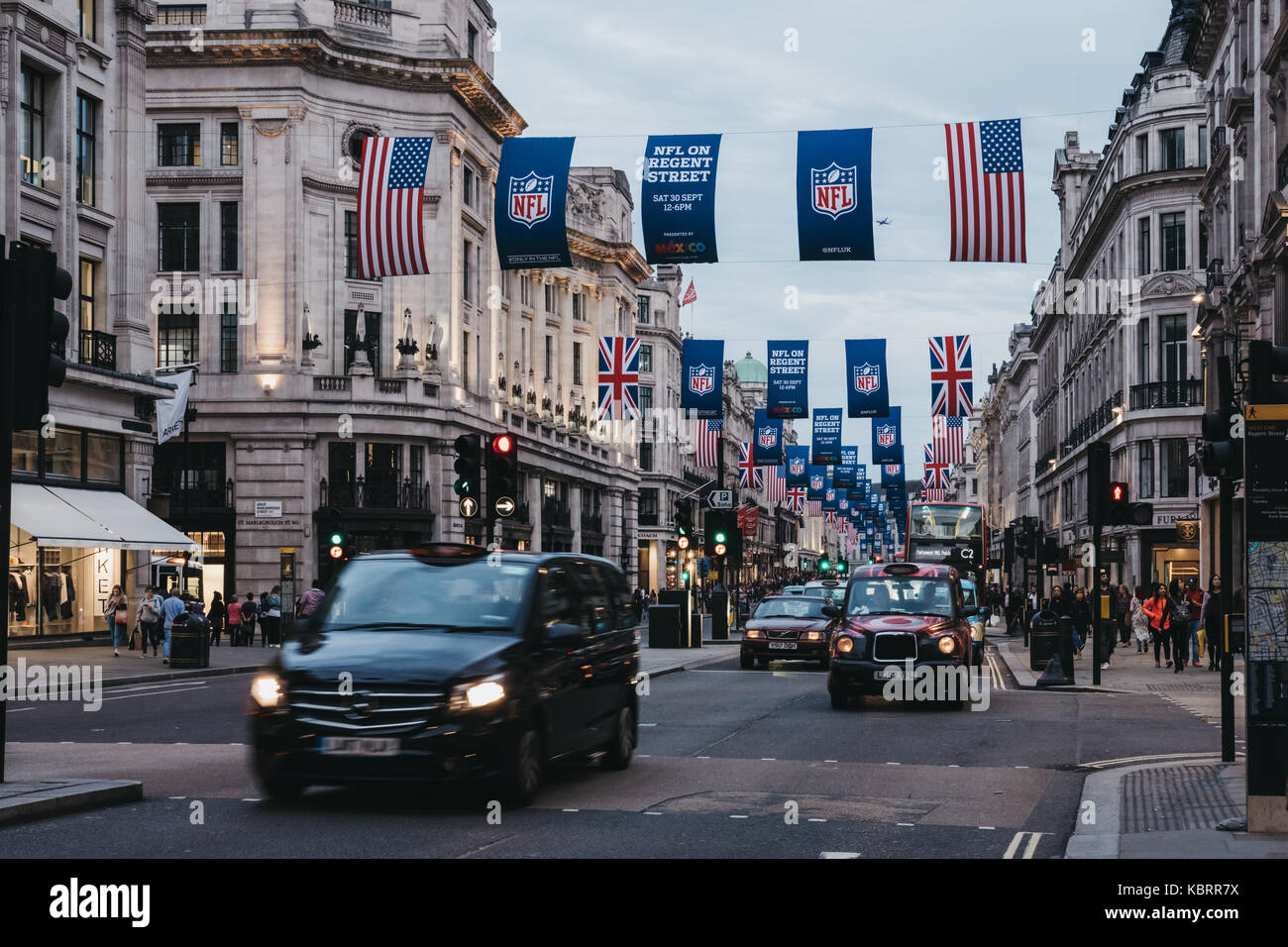 Black taxi and cars on Regent Street, London. The street is decorated with NFL flags to celebrate the event and - Stock Image
