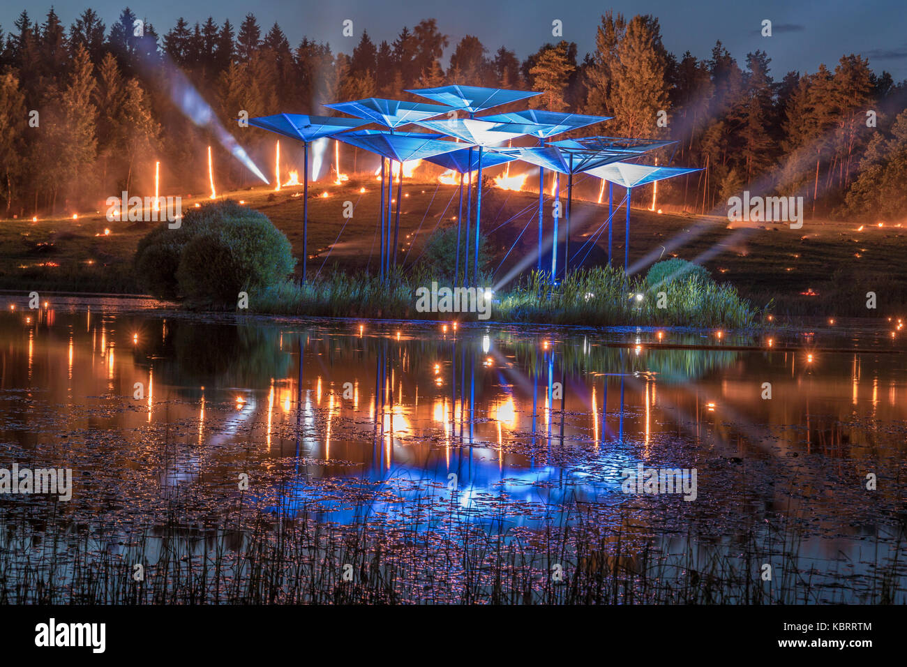Burning fire in the background with searching lights and reflection from the lake Stock Photo