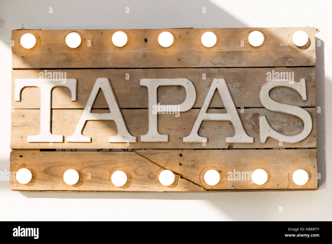 Tapas sign made of wooden planks and light bulbs on top and bottomStock Photo