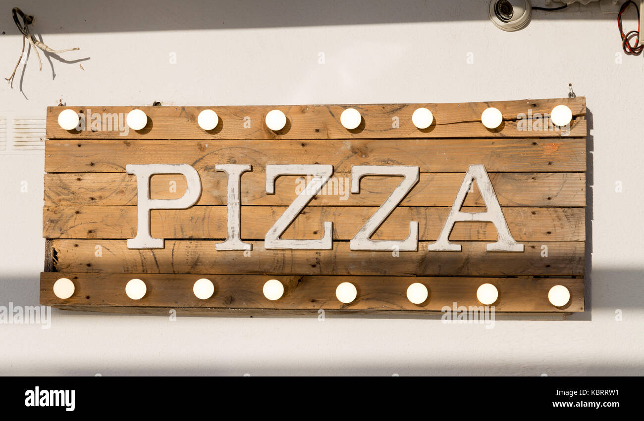 Pizza sign made of wooden planks and light bulbs on top and bottomStock Photo