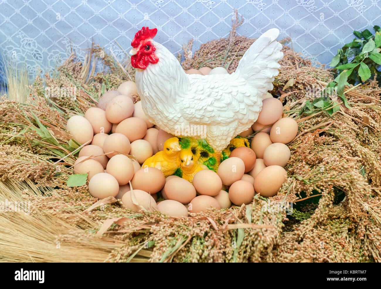Plastic figure of white chicken, chicks and natural eggs - Stock Image