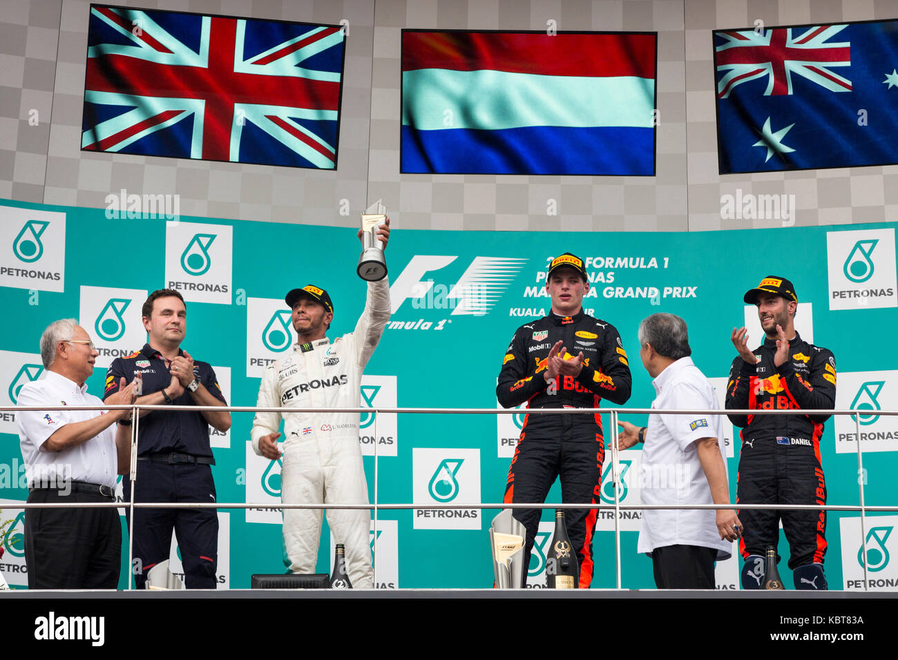 Lewis Hamilton (L) from Mercedes, Max Verstappen (C) and Daniel Ricciardo (R) from RBR TAG Heuer celebrate their victory in the F1 Grand Prix at the Sepang F1 circuit. Verstappen finished the race in the first position, Hamilton came second and Ricciardo won the 3rd place. On October 01, 2017 in Kuala Lumpur, Malaysia. Stock Photo