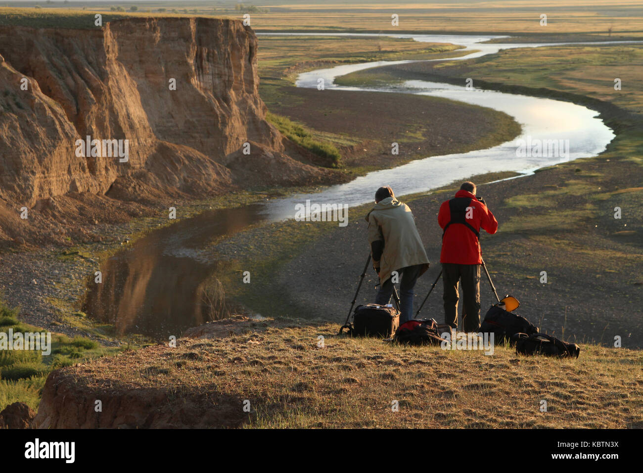 Photographs over the canyon. KHARKHORIN, MONGOLIA, JULY, 11 - Two photographers in the dawn lights over the river, Stock Photo